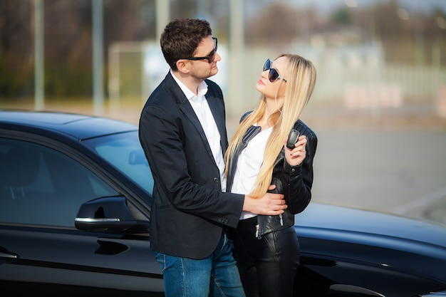 Happy young couple chooses and buying a new car for the family Premium Photo