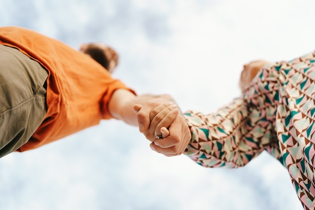 Happy young couple in colorful clothes with sky Free Photo