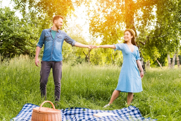 Happy young couple dancing and looking at each other with love in nature Free Photo