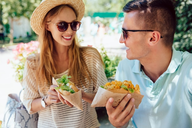 Happy young couple eating hot dog, spending time with pleasure, outdoors. Free Photo