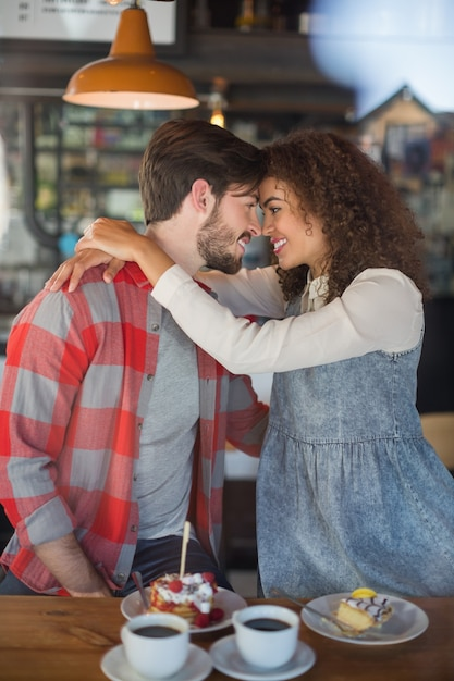 Счастливая молодая пара, обнимая в пабе Premium Фотографии