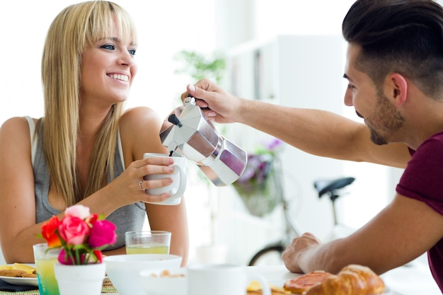 Happy young couple enjoying breakfast in the kitchen. Free Photo