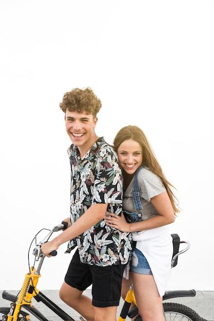 Happy young couple enjoying ride on bicycle against white backdrop Free Photo