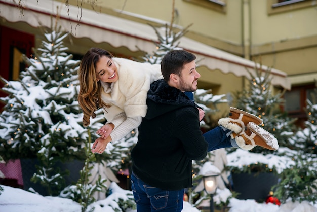 Happy young couple having fun on winter cityscape  of christmas tree with lights. winter holidays, christmas and new year . Premium Photo