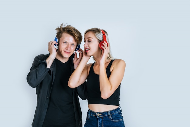 Happy young couple in headphones listening music Free Photo