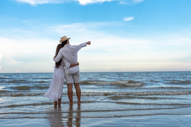 Happy young couple holding each other and laughing with enjoying together on the summer beach. Premium Photo