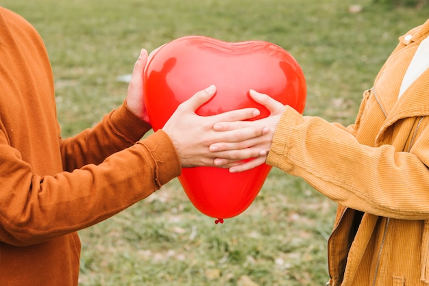Happy young couple holding heart-shaped balloon Free Photo
