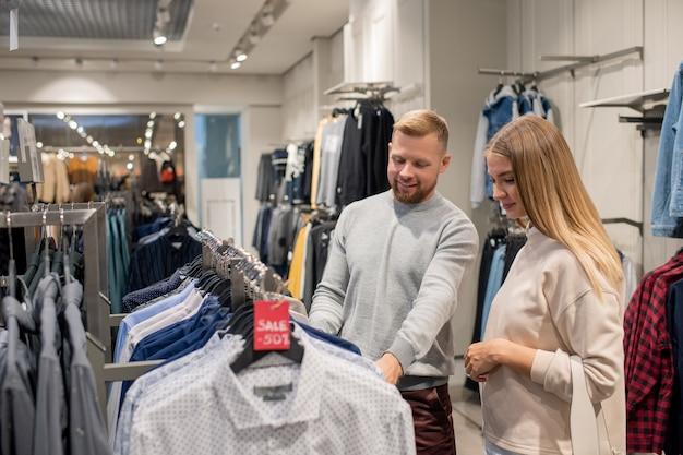 割引でシャツとラックのそばに立って、販売中に新しいものを選択するカジュアルウエアで幸せな若いカップル Premium写真