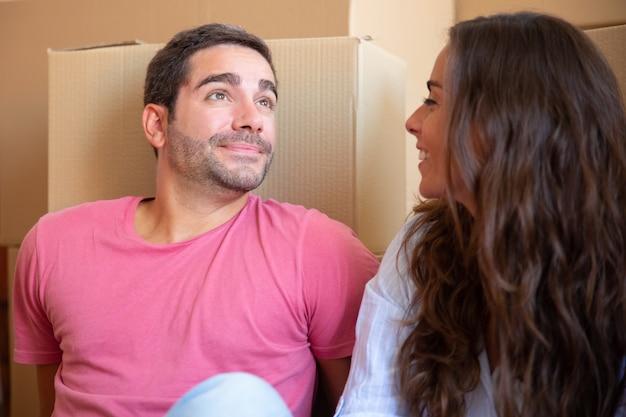 カートンボックスの山の近くの床に座って、新しいアパートに移動を楽しんで愛の幸せな若いカップル 無料写真