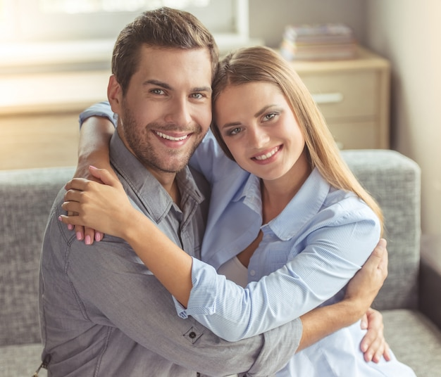 Happy young couple is hugging, looking at camera. Premium Photo