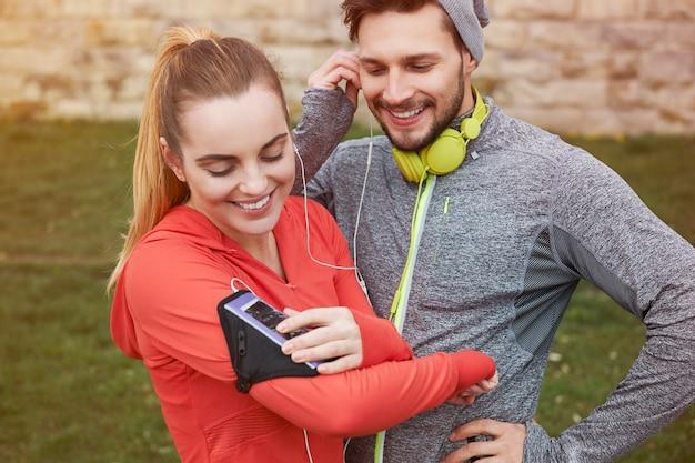 イヤホンで音楽を聴いて幸せな若いカップル 無料写真