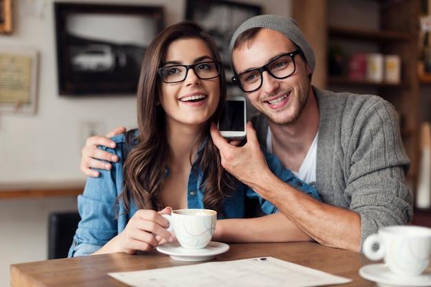 Felice coppia giovane ascoltando la voce dal telefono cellulare Foto Gratuite