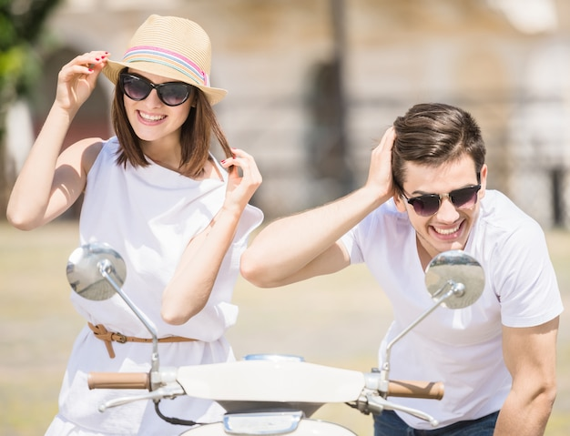 Happy young couple looking at front view mirrors of scooter. Premium Photo