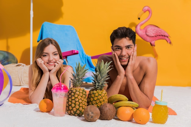 Happy young couple lying with fruit on beach in studio Free Photo
