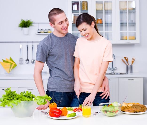 Счастливая молодая пара вместе готовить завтрак на кухне Бесплатные Фотографии