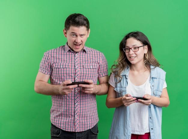 Felice giovane coppia uomo e donna utilizzando gadget sorridente in piedi sopra la parete verde Foto Gratuite