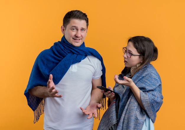 Felice giovane coppia uomo e donna con coperte sostenendo in piedi oltre il muro arancione Foto Gratuite