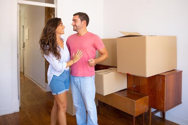 Giovani coppie felici che si spostano nel nuovo appartamento, in piedi vicino a mobili e scatole di cartone e discutono di disimballaggio Foto Gratuite