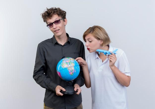행복 한 젊은 관광객 남자와여자가 흰 벽 위에 함께 서있는 글로브와 장난감 공기 비행기를 들고 무료 사진
