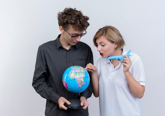 Счастливая молодая пара туристов мужчина и женщина, держащая глобус и игрушечный самолет вместе над белой Бесплатные Фотографии