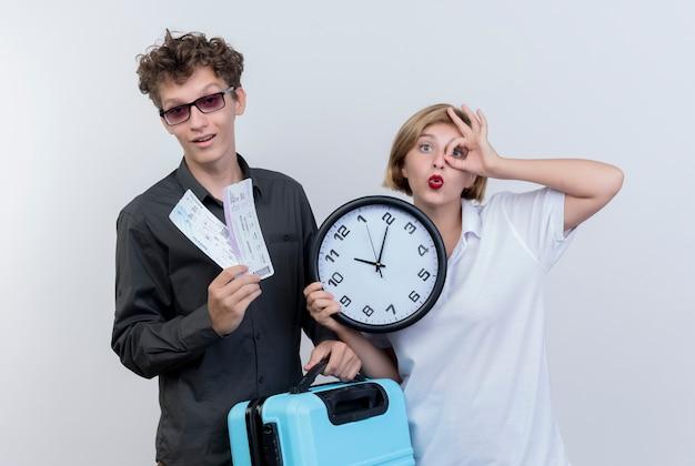 航空券とスーツケースを持っている観光客の幸せな若いカップルは、白い壁の上に立って大丈夫歌う壁時計を持っている女性と一緒に 無料写真