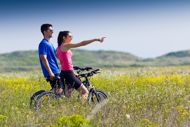 happy young couple on a bike ride in the countryside photo free