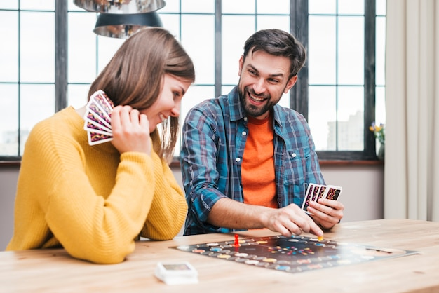 Happy young couple playing the boardgame on wooden table Free Photo