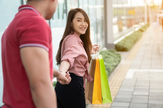 Happy young couple of shoppers walking in the shopping street towards in black friday shopping Premium Photo
