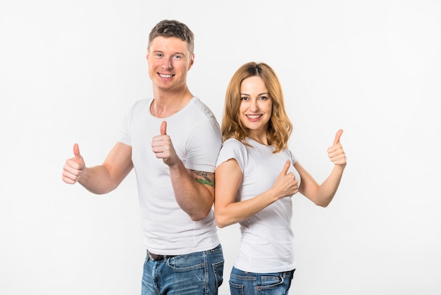 Happy young couple showing thumb up sign against white background Free Photo