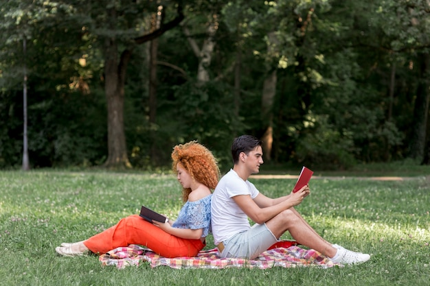Happy young couple sitting back to back on a picnic blanket Free Photo