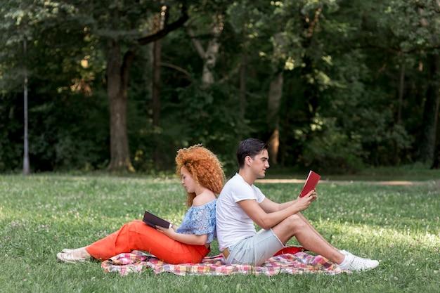 ピクニック毛布の上に背中合わせに座って幸せな若いカップル 無料写真