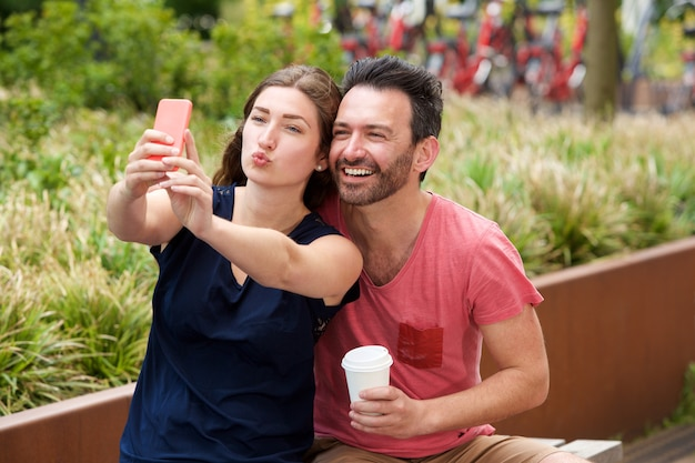 Happy young couple sitting together taking selfie on smart phone Premium Photo