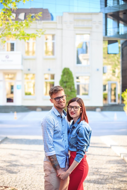 Happy young couple standing at street of city and laughing on the bright sunny day Free Photo