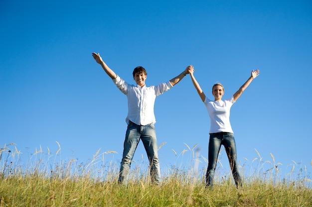手を上げて夏の牧草地に一緒に立っている幸せな若いカップル 無料写真