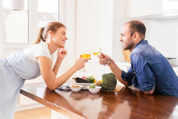 Happy young couple toasting the wineglasses with fresh salad on table Free Photo