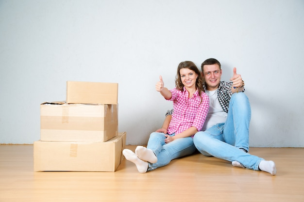 Happy young couple unpacking or packing boxes and moving into a new home. Premium Photo