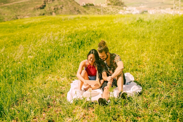 Happy young couple using tablet in glade Free Photo