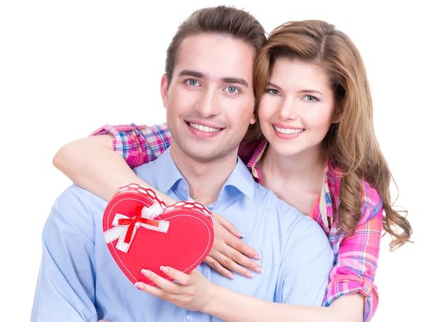 白い背景で隔離のスタジオで贈り物と幸せな若いカップル 無料写真