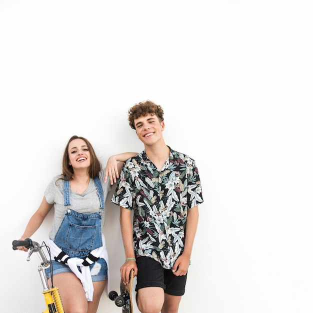Happy young couple with bicycle and skateboard on white backdrop Free Photo