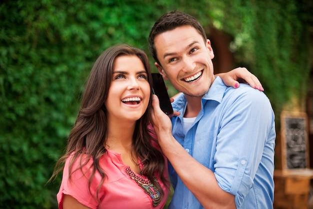 Felice giovane coppia con smart phone Foto Gratuite