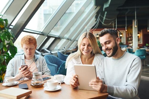 タッチパッドがビデオチャットで話したり、友人とカフェでリラックスしながらオンラインで映画を見たりする幸せな若いカップル Premium写真