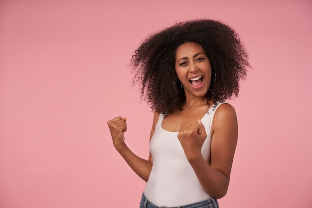 Happy young curly female with casual hairstyle with wide joyful smile, celebrating win of her favourite team, isolated on pink with raised fists Free Photo