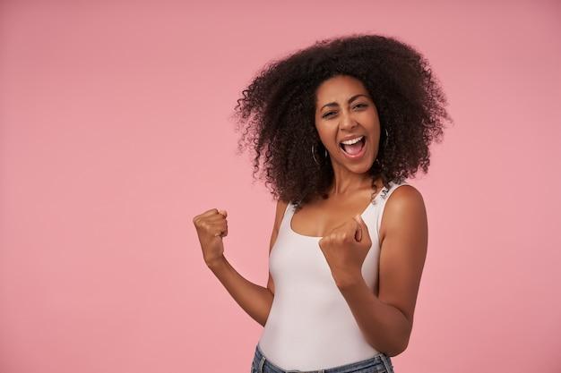 Счастливая молодая кудрявая женщина с непринужденной прической с широкой радостной улыбкой празднует победу своей любимой команды, изолированная на розовом с поднятыми кулаками Бесплатные Фотографии