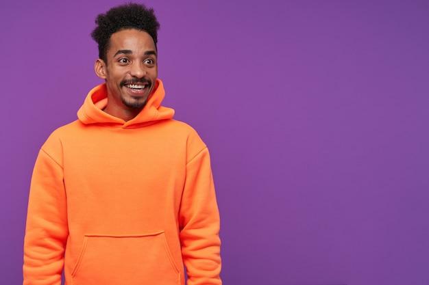 幸せな若いかわいい暗い肌のブルネットの男ひげは嬉しい驚きと広い笑顔で喜んで、紫色のポーズをとっている間カジュアルな服を着ています 無料写真