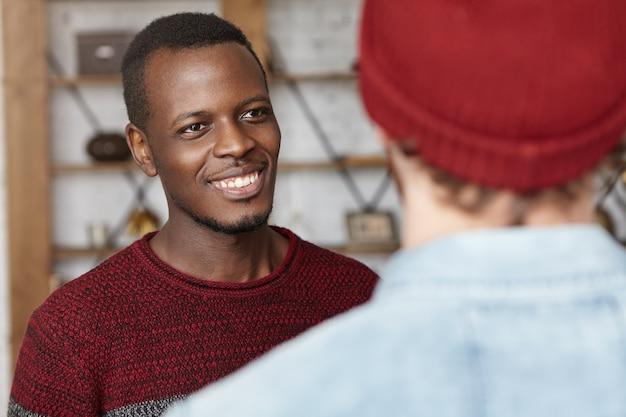 Счастливый молодой темнокожий мужчина весело улыбается, глядя на своего неузнаваемого стильного друга Бесплатные Фотографии
