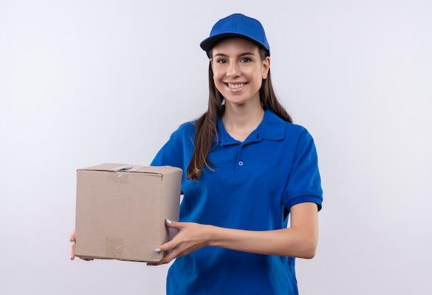 Felice giovane ragazza di consegna in uniforme blu e berretto tenendo il pacchetto scatola sorridente fiducioso Foto Gratuite