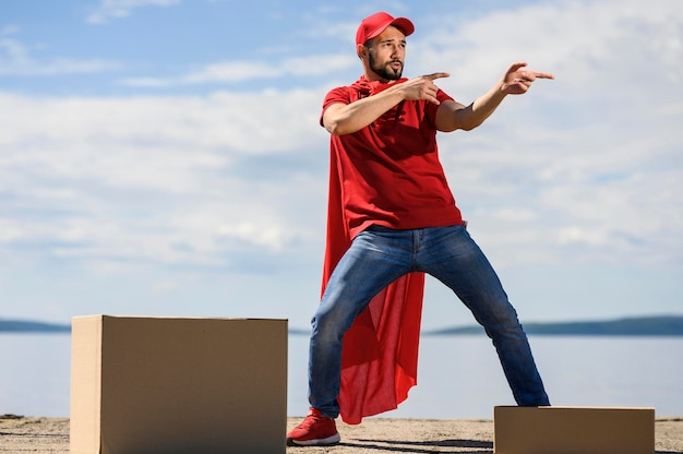 Felice giovane uomo di consegna che indossa il mantello da supereroe Foto Gratuite