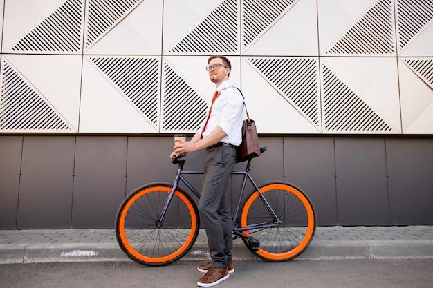 家に帰りながら現代建築の外観に対して都市環境に立っている自転車で幸せな若いエレガントな男 Premium写真
