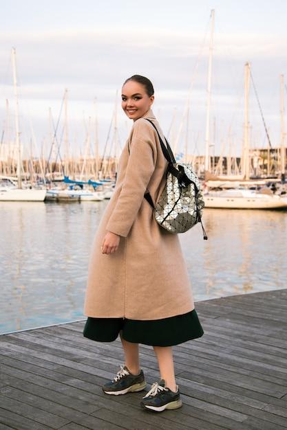 シーズンの観光時間の半ば、コートスニーカーとバックパックを身に着けているバルセロナの高級ヨットクラブで歩いて幸せな若いエレガントな女性。 無料写真