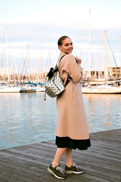 Felice giovane donna elegante che cammina allo yacht club di lusso di barcellona, indossando scarpe da ginnastica cappotto e zaino, tempo turistico di mezza stagione. Foto Gratuite
